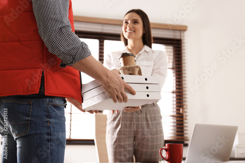 Courier giving order to young woman in office  Food delivery