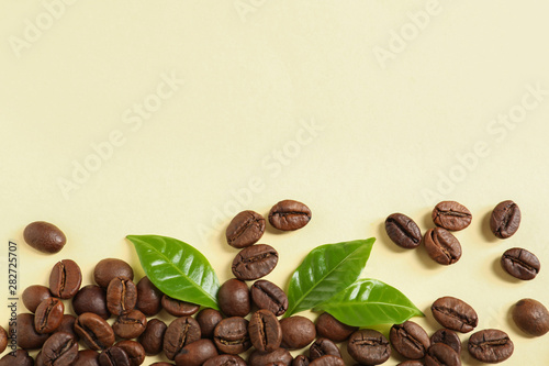 Fresh green coffee leaves and beans on light yellow background, flat lay. Space for text - 282725707