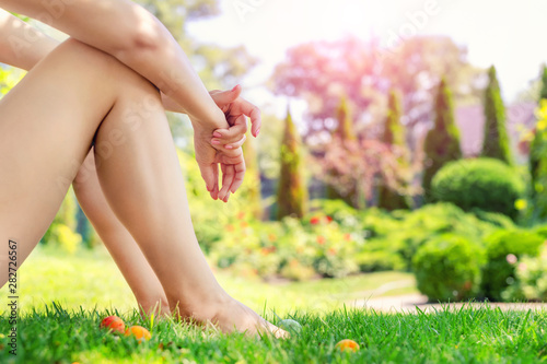 Foto auf Gartenposter Gelb Schwefelsäure Young adult slim sexy woman sitting on green grass in park. Close-up girls barefoot legs and hands on lawn meadow in fruit garden. Landsacape design and gardening. Healthcare and relaxation cocept
