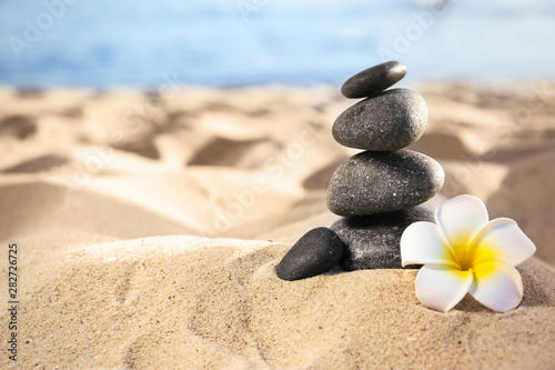 Acrylic Prints Zen Stack of dark stones and beautiful flower on sandy beach near sea, space for text. Zen concept