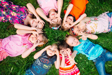 A group of children lying on the green grass in the Park. The interaction of ...