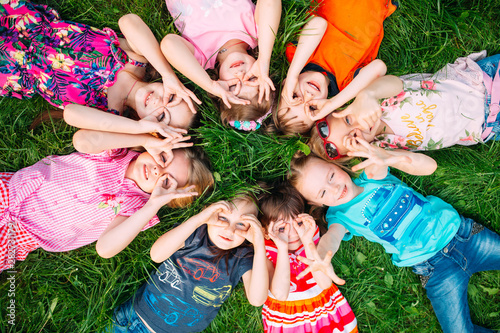 Fototapeta A group of children lying on the green grass in the Park. The interaction of the children. obraz