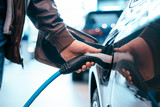 Fototapeta Do pokoju - Human hand is holding Electric Car Charging connect to Electric car