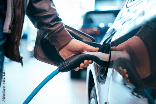 Foto Human hand is holding Electric Car Charging connect to Electric car