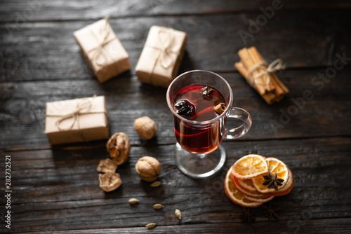delicious and fragrant mulled wine on the table, anise, cinnamon and orange, Christmas gifts in craft paper