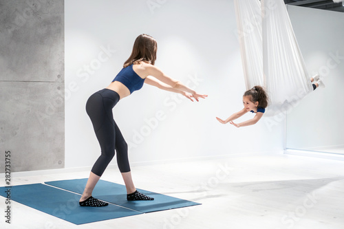 Mom and Daughter are doing yoga. Family in a gym.