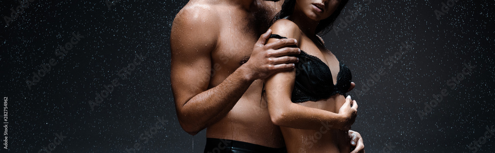 Fototapeta panoramic shot of sexy man hugging woman in lingerie under raindrops on black