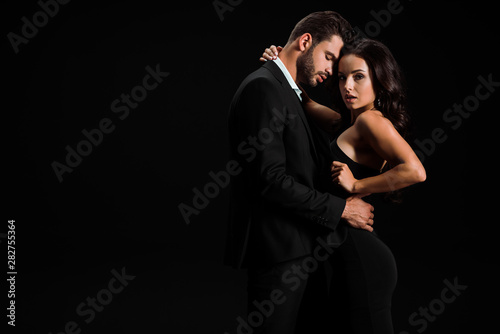 Pinturas sobre lienzo  attractive woman hugging handsome bearded man while standing isolated on black