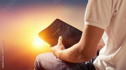Man reading old Bible book on background Wallpaper Mural