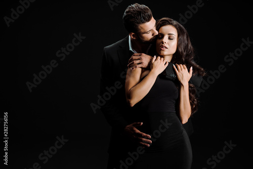 Fotomural  handsome man kissing beautiful girl with closed eyes isolated on black