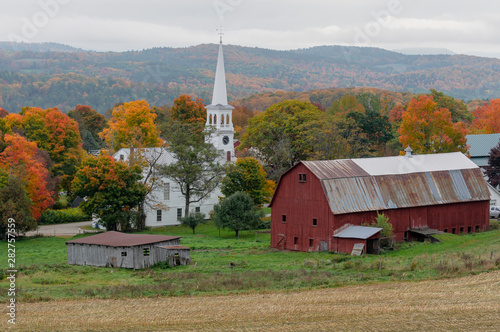 A small church sits on a farm next to a weathered red barn during Autumn in Vermont