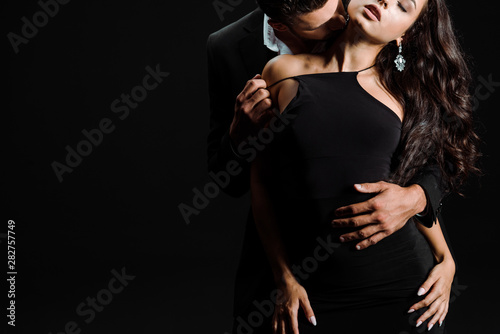 canvas print motiv - LIGHTFIELD STUDIOS : cropped view of passionate man kissing woman in dress isolated on black