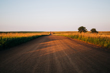 A Long Country Highway Road In Rural North Dakota With A Bright Blue Sky With Clouds In The Horizon