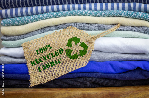 Recycle clothes icon on fabric label with 100% Recycled text Fototapeta