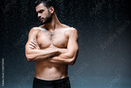 Fototapeta  handsome wet man standing with crossed arms under raindrops on black
