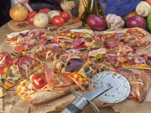 Pizza on thin dough.With slices of salami and ham ,olives and tomatoes. © Игорь Кислинский
