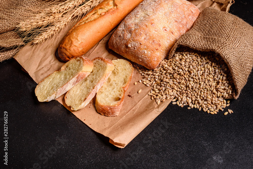 Fotobehang Brood Fresh fragrant bread with grains and cones of wheat against a dark background. Assortment of baked bread on wooden table background