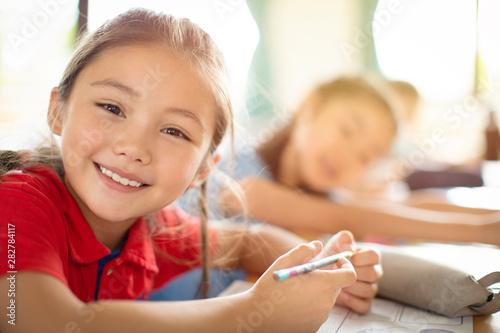 Staande foto Wanddecoratie met eigen foto Smiling elementary school kids in classroom