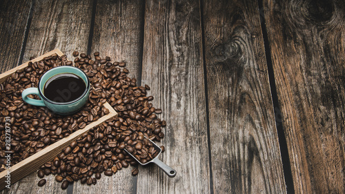 Wall Murals Cafe cup of coffee and beans on brown wooden table with text space
