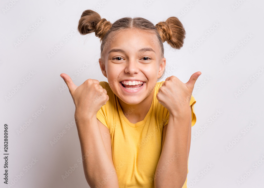 Fototapety, obrazy: Portrait of teen girl making Thumb up Gesture, on gray background. Beautiful caucasian young teenager smiling. Happy cute child showing success sign.