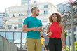 Mix raced couple of tourists walking around hotels. Young Latin man and black woman in casual enjoying walk, talking, discussing news. Travelers concept