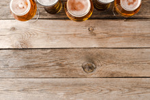 Overhead Shot Of Beer Glasses On Wooden Table.
