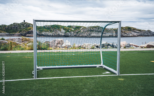 Empty training gate for classic fotbal on green grass playground on Lofoten Islands surrounded by rocks and stones Wallpaper Mural