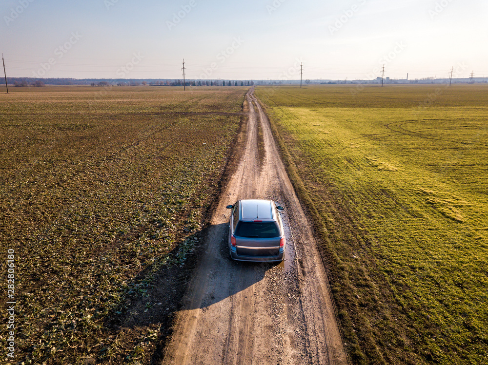 Fototapeta Aerial view of car driving by straight ground road through green fields on sunny blue sky copy space background. Drone photography.