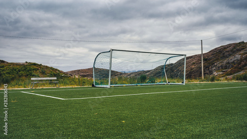 Empty training gate for classic fotbal on green grass playground on Lofoten Islands surrounded by rocks and stones Canvas Print