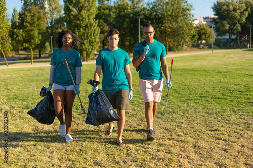 Serious volunteers carrying garbage from city park. Young woman and men walking through city lawn, holding rakes and plastic bags. Trash removal concept