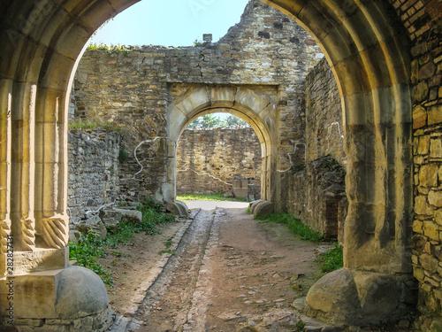 Photo  Portal in Romanesque style, corridor between stone walls
