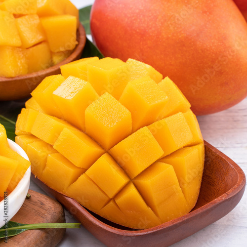 Poster Pays d Asie Fresh chopped mango on a tray and bright rustic wooden background. Tropical summer fruit design concept, close up, macro, copy space.