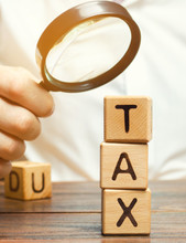 Wooden Blocks With The Word Tax And A Magnifying Glass In The Hands Of A Businessman. The Concept Of Studying The Size Of Taxes. Taxation. Time To Pay Taxes. Tax On Personal Income. Agent. Taxpayer