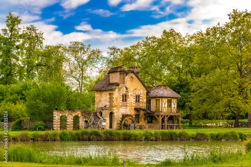 Picturesque view of the Mill, a rustic building in the Queen's Hamlet, surrounded by trees under a blue sky in front of a lake in the park of the Château de Versailles built for Marie Antoinette Canvas Print