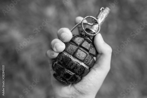 Fotomural Closeup top view of white kid hand holding real old grenade