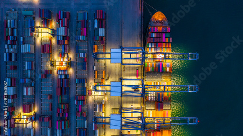 Foto auf AluDibond Shanghai Container ship working at night, Business import export logistic and transportation of International by container ship in the open sea, Aerial view container ship loading and unloading at night.