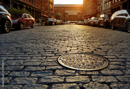 Fotografia, Obraz Sunlight shining on a cobblestone street and manhole cover in New York City