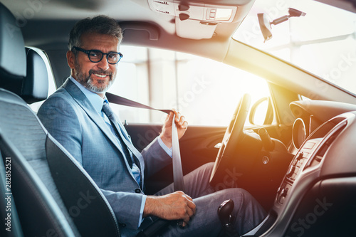 businessman putting seat belt in car Fototapet