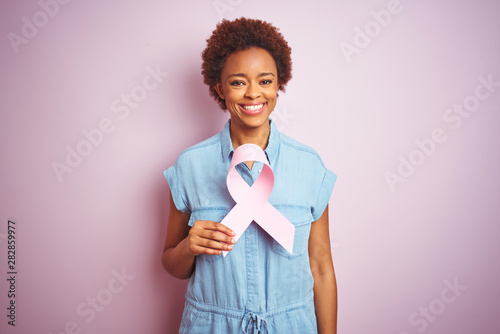 Fotografering Young african american woman holding brest cancer ribbon over isolated pink back