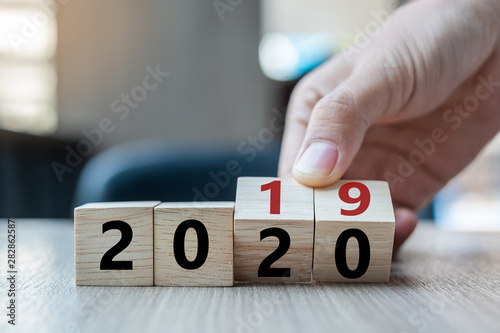 Fotografía  Business man hand holding wooden cube with flip over block 2019 to 2020 word on table background