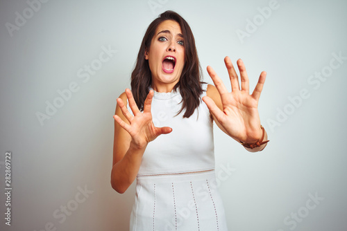 Fotografía  Young beautiful woman wearing dress standing over white isolated background afraid and terrified with fear expression stop gesture with hands, shouting in shock