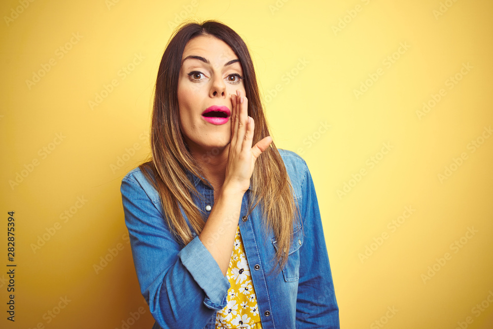Fototapeta Young beautiful woman standing over yellow isolated background hand on mouth telling secret rumor, whispering malicious talk conversation