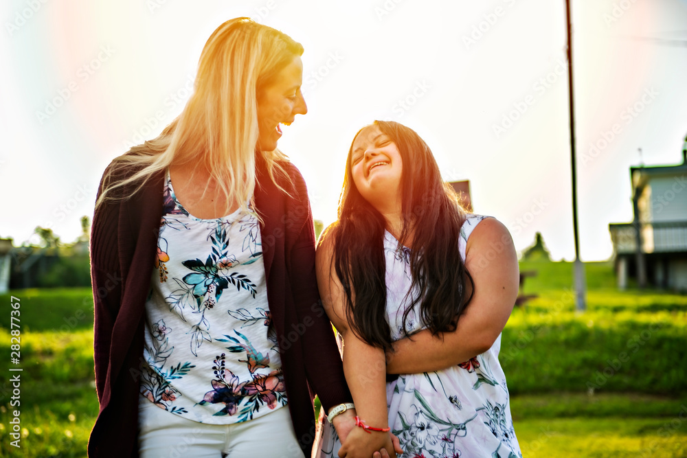 Fototapeta A Portrait of trisomie 21 adult girl smilin outside at sunset with family friend