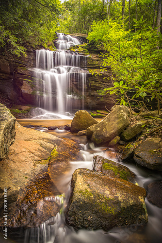 Gorgeous springtime waterfall in the mountains of North Carolina showing the green foliage.