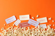 canvas print picture - Flat lay composition with popcorn and tickets on orange background, copy space