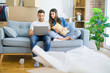Young beautiful couple relaxing sitting on the sofa of new house using computer laptop with a confident expression on smart face thinking serious