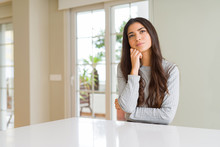 Young Beautiful Woman At Home With Hand On Chin Thinking About Question, Pensive Expression. Smiling With Thoughtful Face. Doubt Concept.