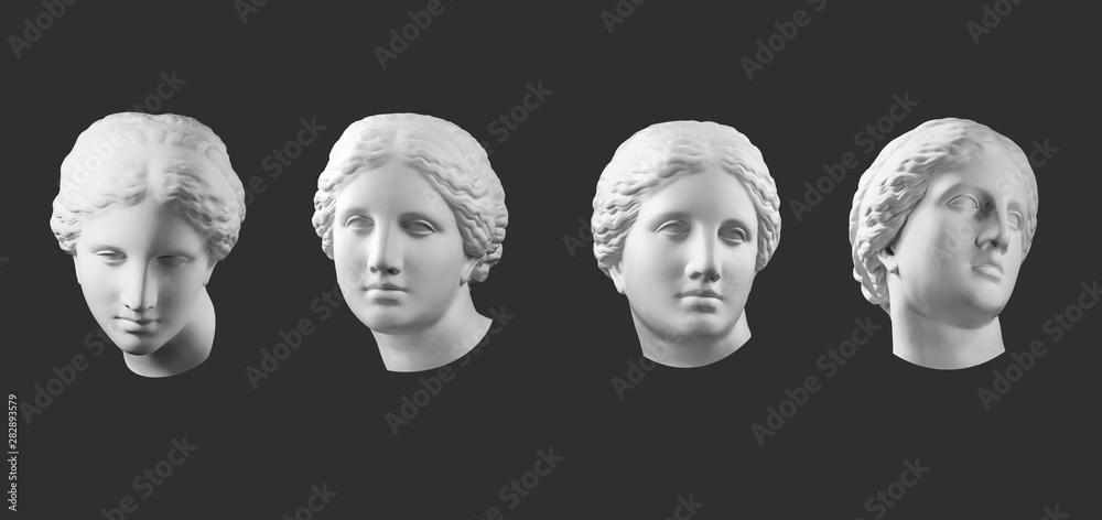 Fototapeta Four gypsum copy of ancient statue Venus head isolated on black background. Plaster sculpture woman face.