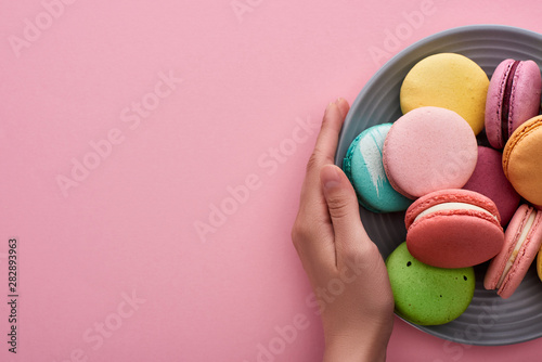 Foto auf Leinwand Texturen cropped view of woman holding plate with multicolored delicious French macaroons on pink background with copy space