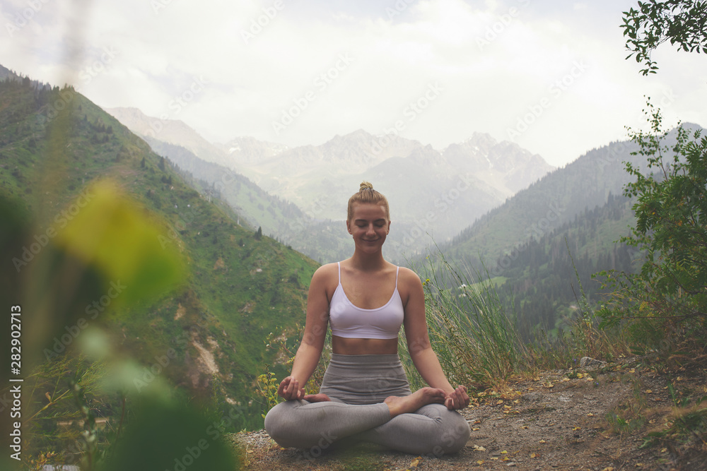 Fototapeta Sport girl doing yoga in mountains beautiful landscape. Young woman leads healthy lifestyle, meditates, relaxes lotus position in bright sportswear on nature